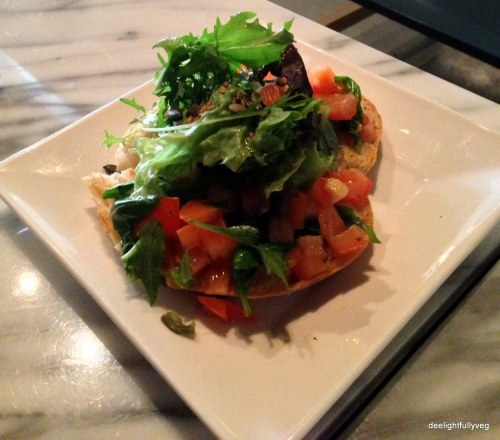 Herb salad on tomato bruschetta